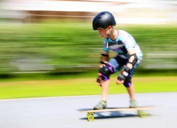 Kind übt Longboard fahren mit Helm und Schoner