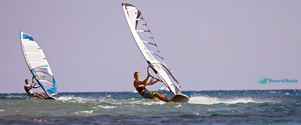 Zwei Surfer hängen im Trapez an ihrem Windsurfboard