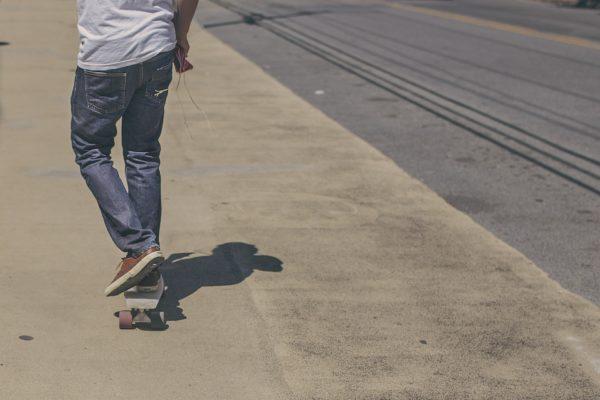Junger mann auf dem Longboard