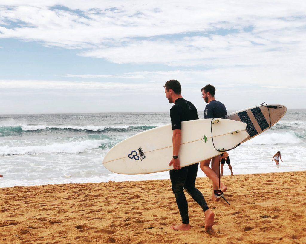 Zwei Männer gehen mit dem Surfbrett zum Wasser