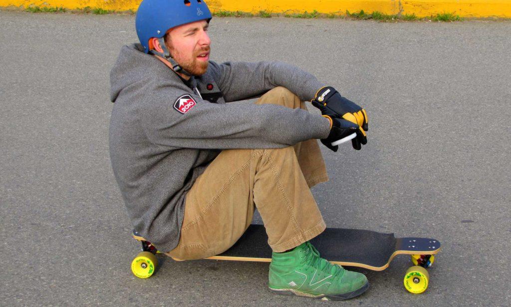 Anfäger sitzt auf Longboard