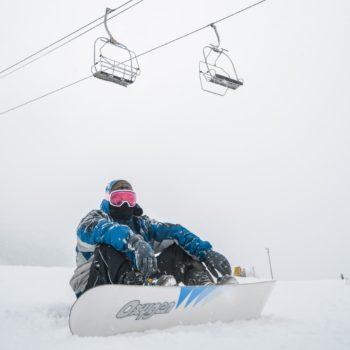 Snowboarder sitzt und erholt sich.