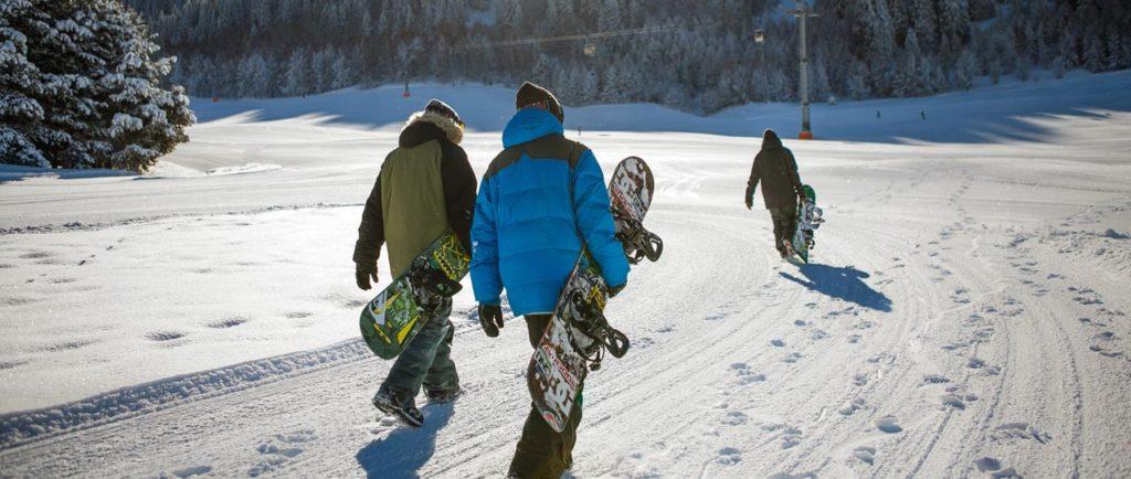 Drei Snowboarde tragen ihr Board zur Piste
